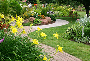 Landscape design with flower beds and stone walkway