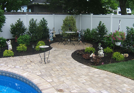 Landscape designed with small stone patio seating area within grass and trees