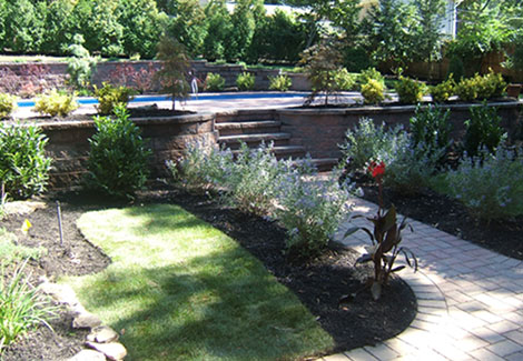 Landscaping around stone steps and elevated patio