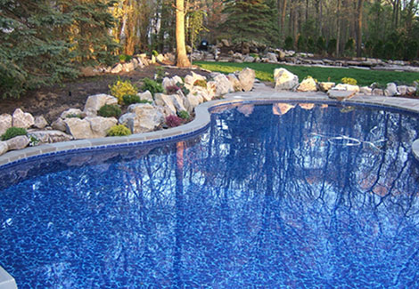 Kidney shaped in ground pool with stone work and tree beds
