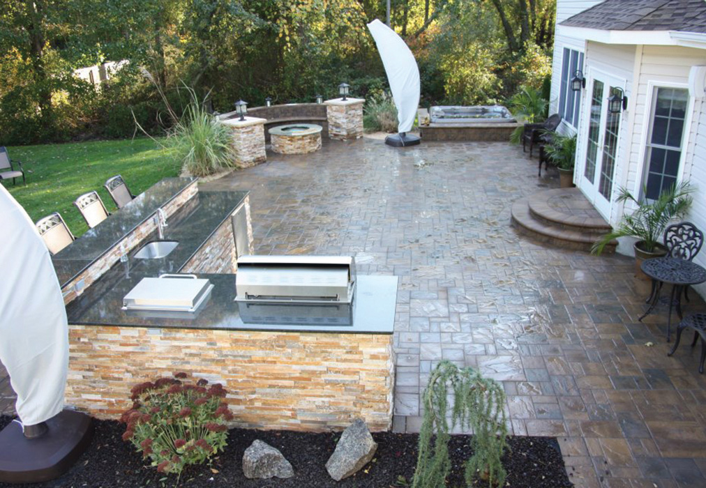 large stone patio with seating area, outdoor kitchen, and fire pit