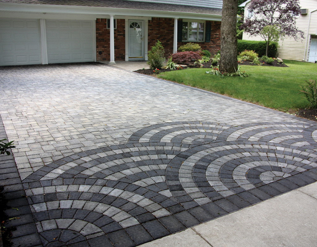 Masonry driveway with scalloped designs on the end of the driveway