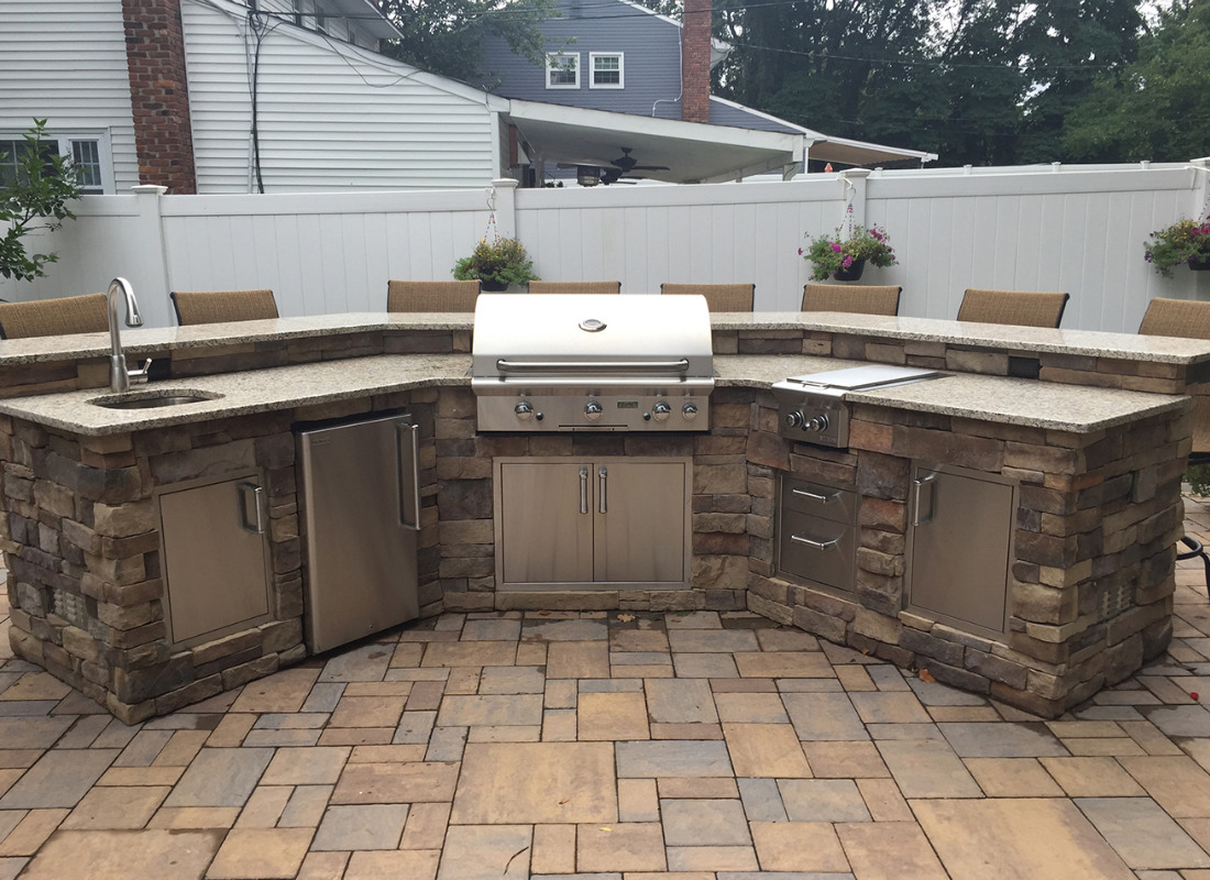 outdoor kitchen with sink, grill, and fridge