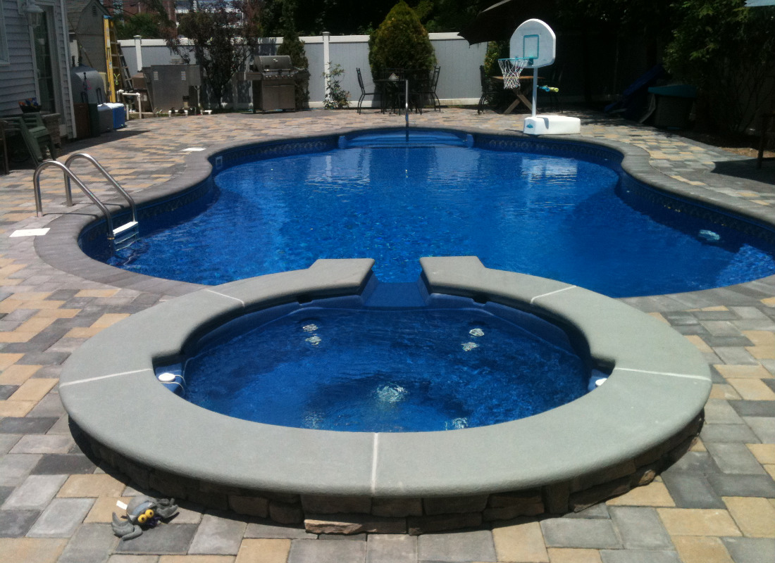 In-ground pool with attached hot tub. Hot tub has water feature spilling into the pool