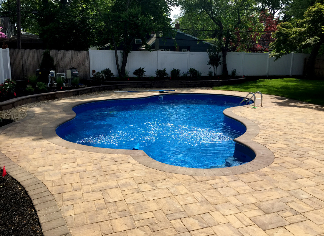 Odd shaped pool with beige colored masonry work