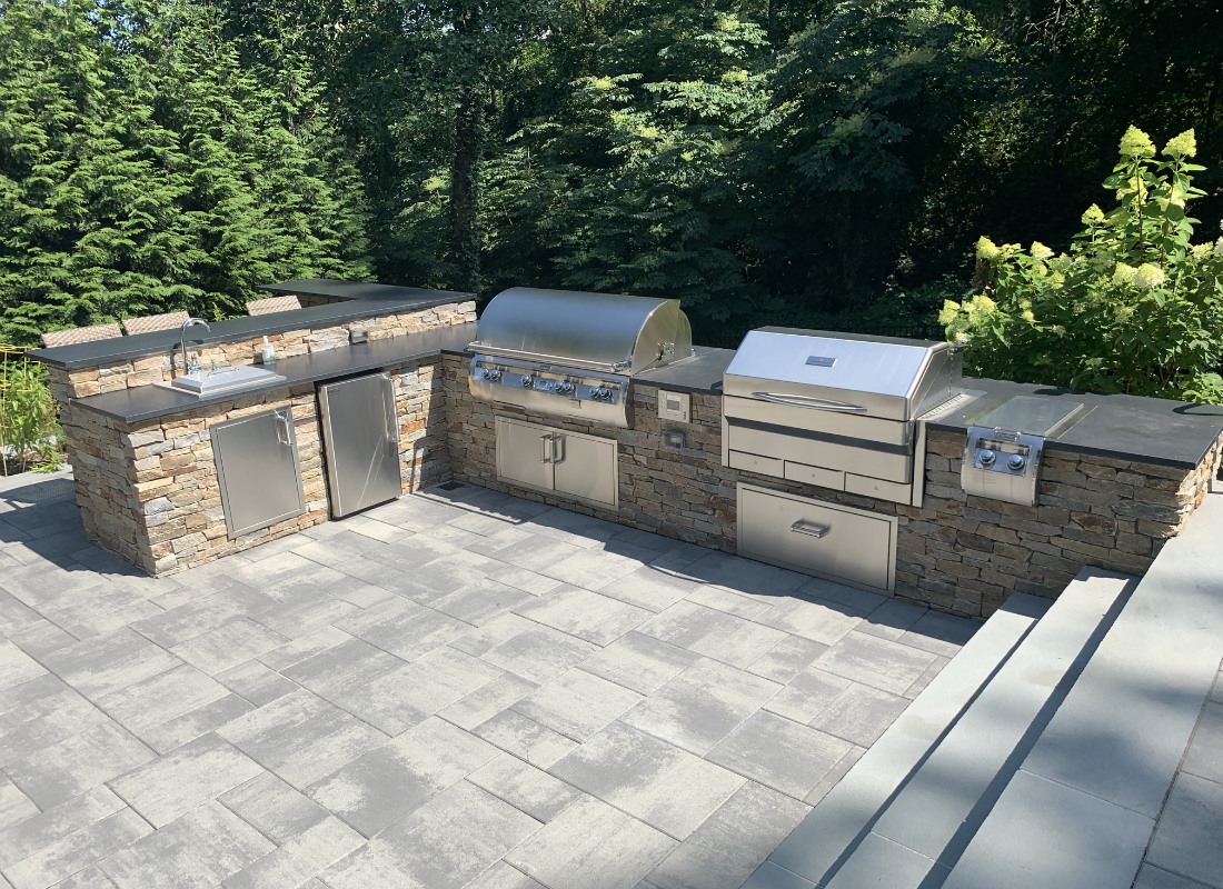 Large outdoor kitchen with sink, BBQ, smoker, and storage