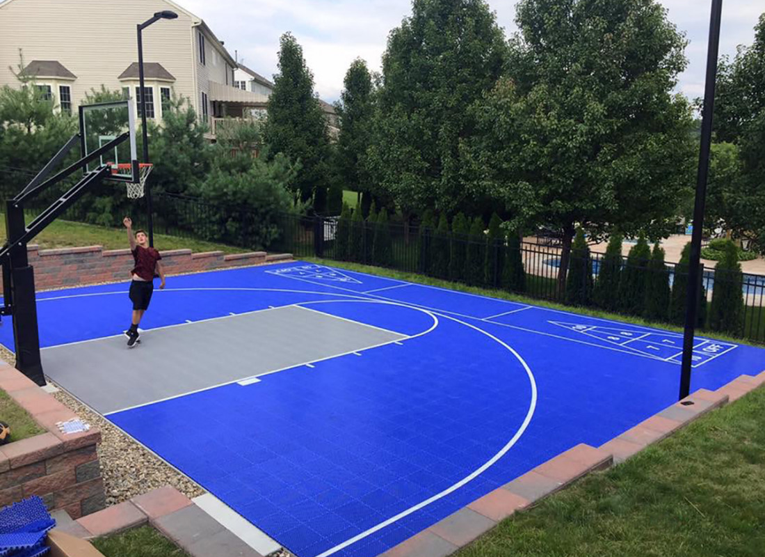 Bright blue half basketball court with shuffle board on the other side