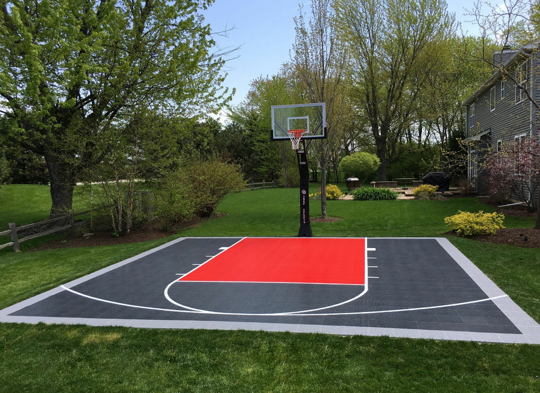 Gray and red half basketball court in a backyard