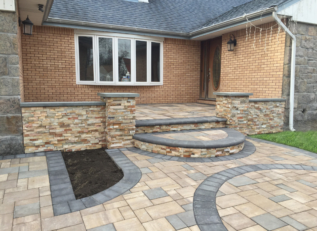rectangular stone porch leading down to stone walkway and driveway