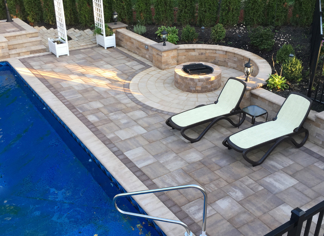 Side of pool with brick fire pit and two lounge chairs