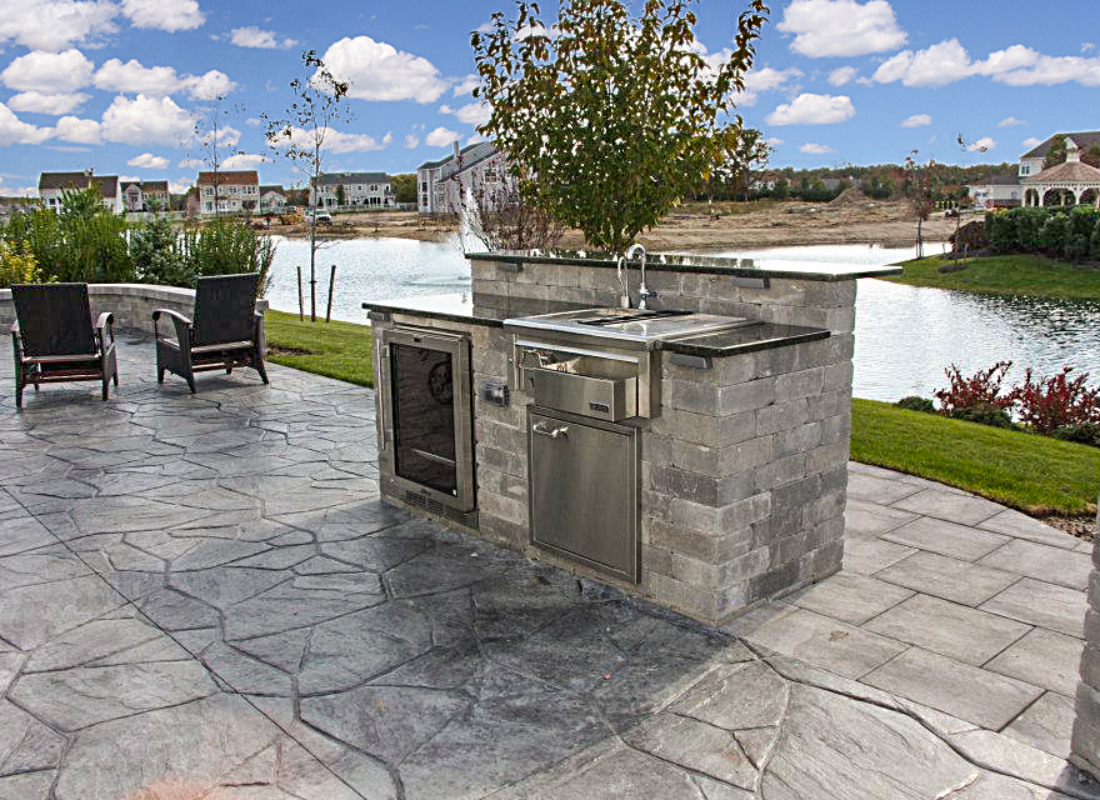 small outdoor kitchen with sink and refrigerator