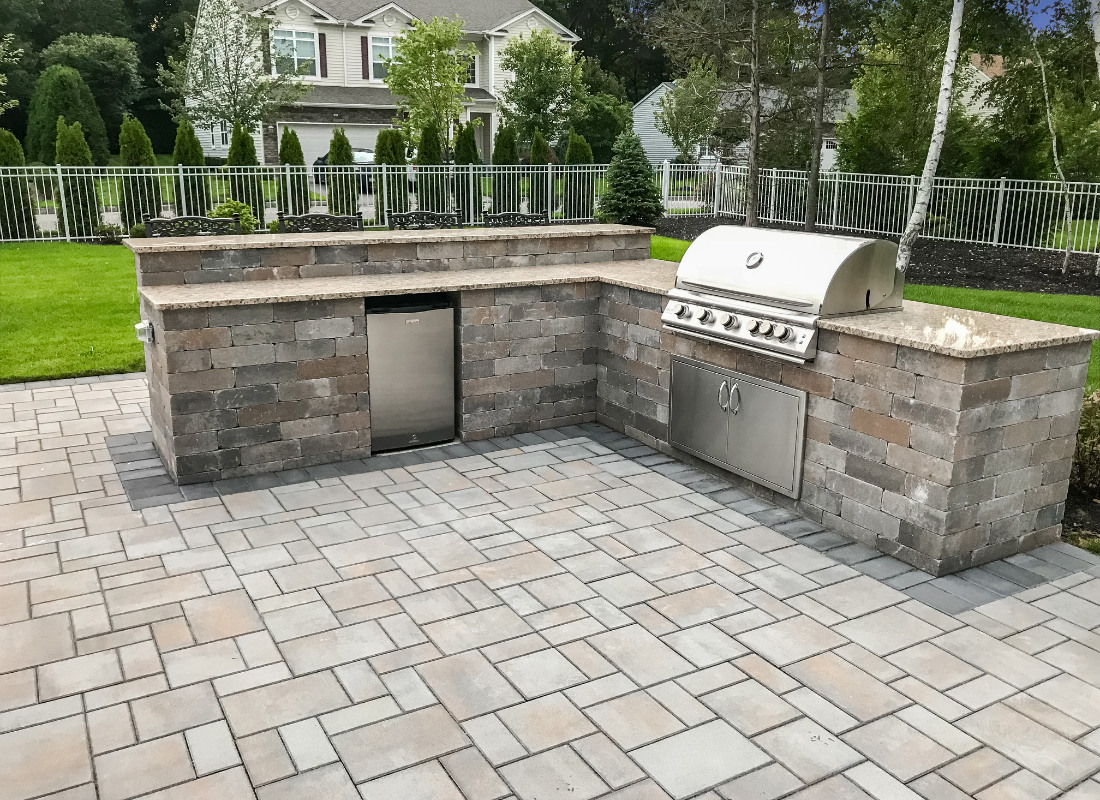 L-shaped stone outdoor kitchen with fridge and grill