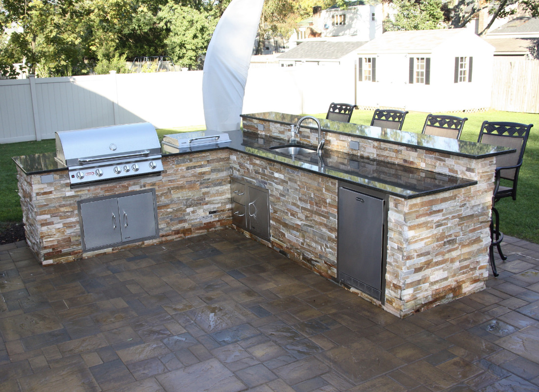 Large L-shaped outdoor kitchen with BBQ, stove top, sink, storage drawers, and refrigerator