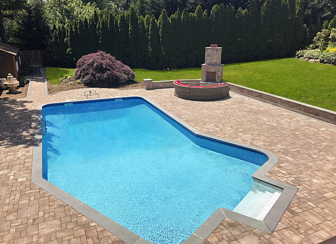 In-ground pool with patio built around it and custom fire pit installed in the far corner