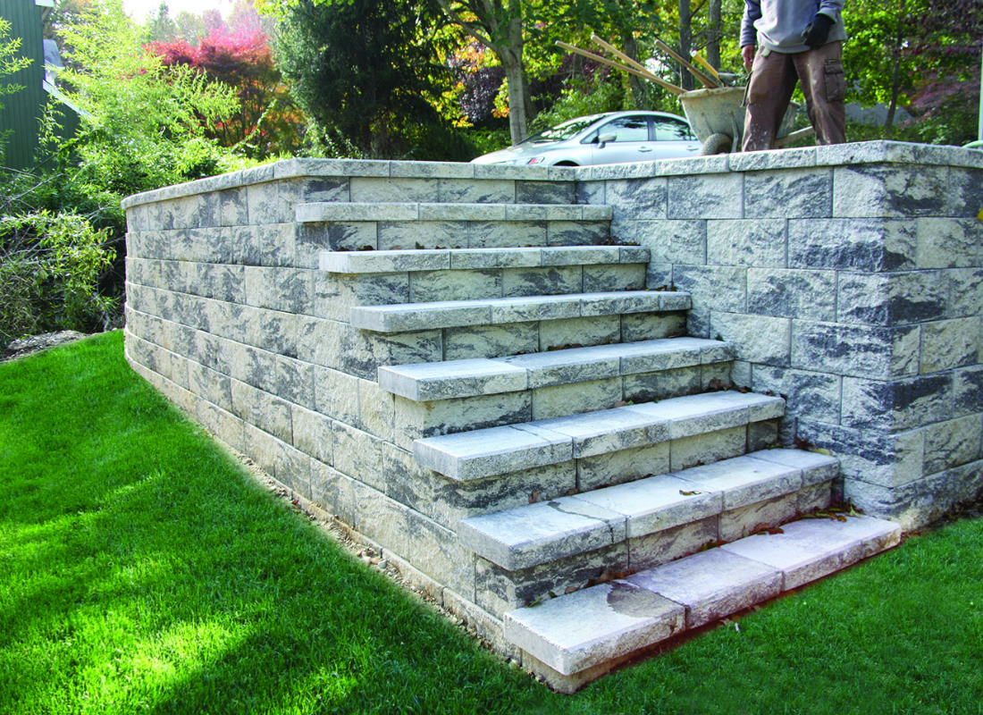 gray stone retaining wall and staircase to elevate to driveway from the home