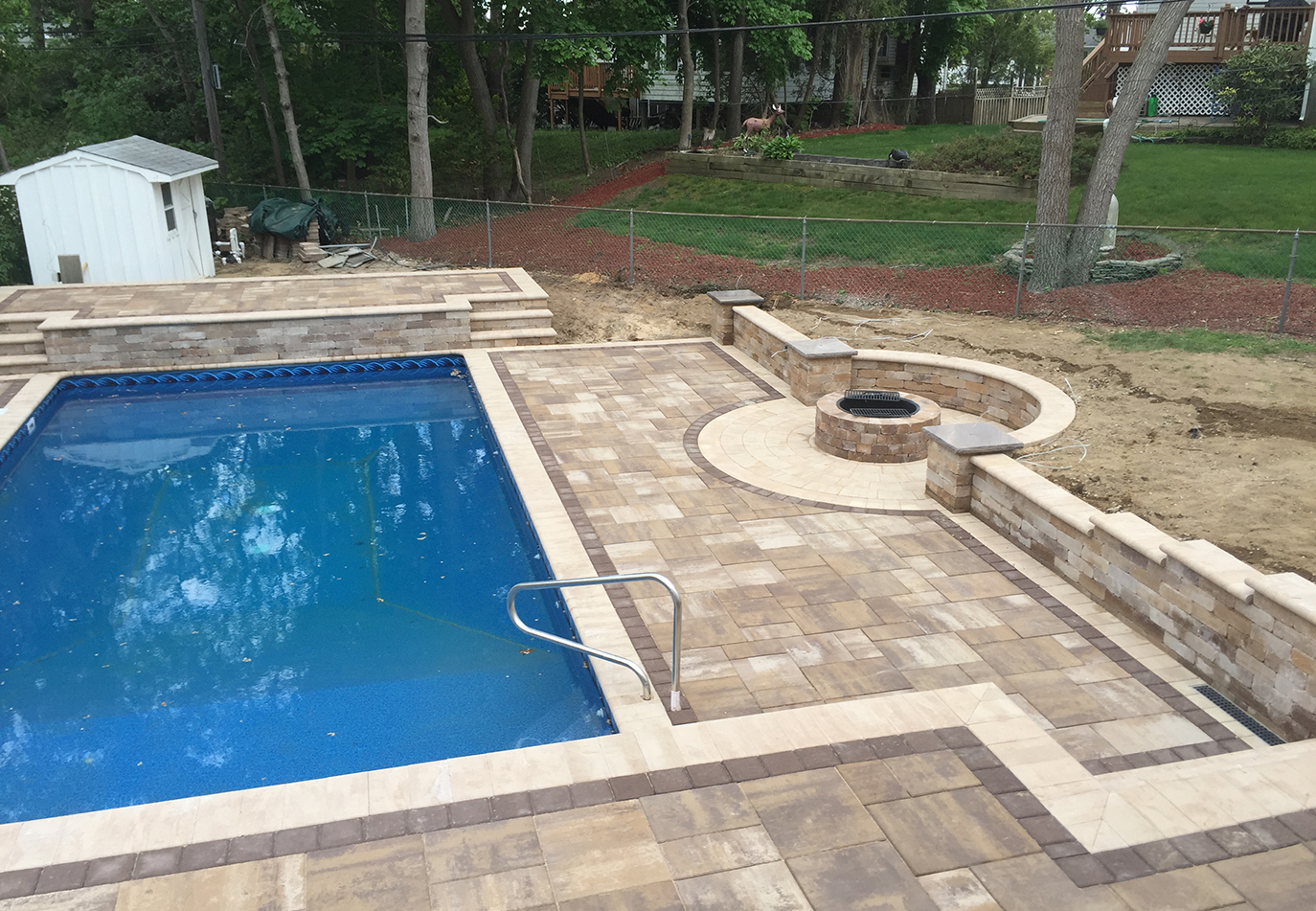 Masonry patio around pool with built in fire pit and stone seating wall