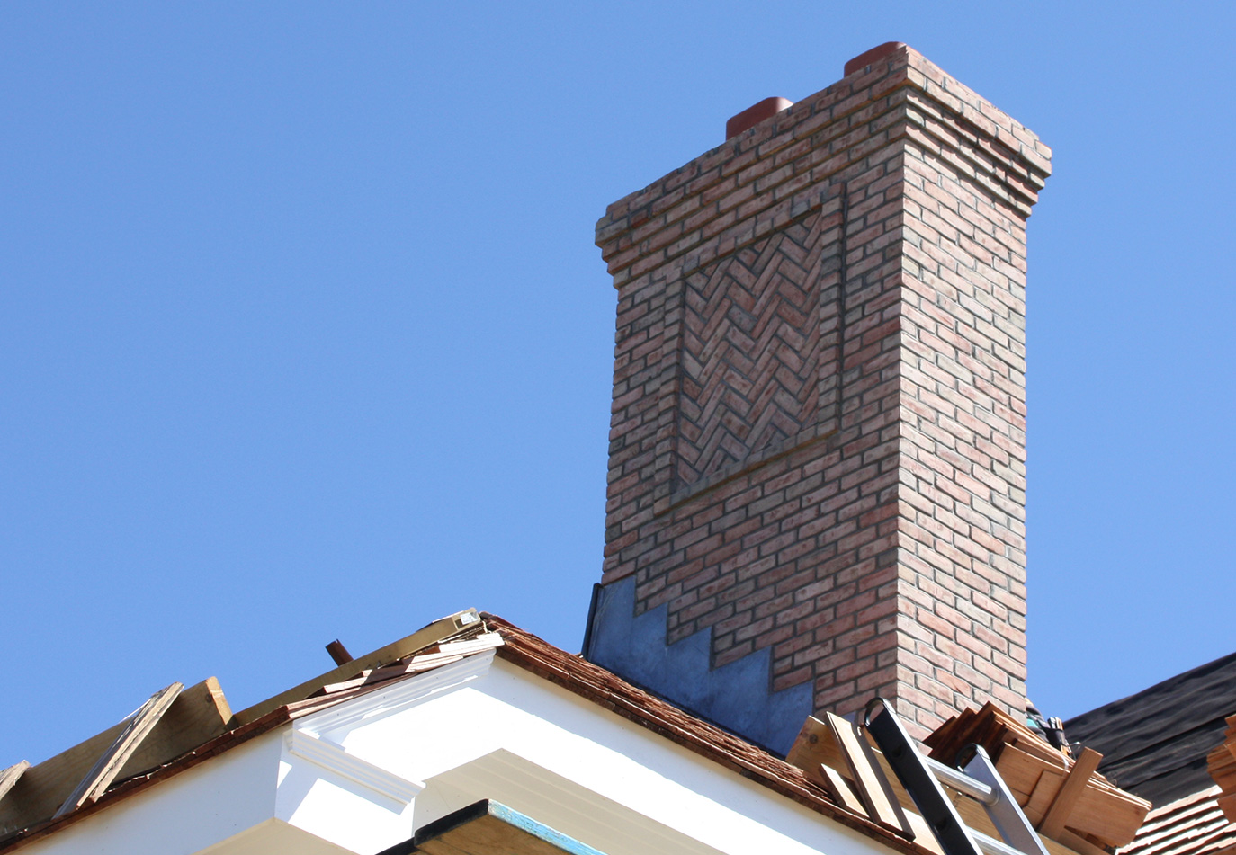 brick chimney being repaired on the roof of the house