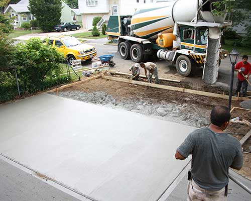 workers installing a concrete driveway for a Long Island home