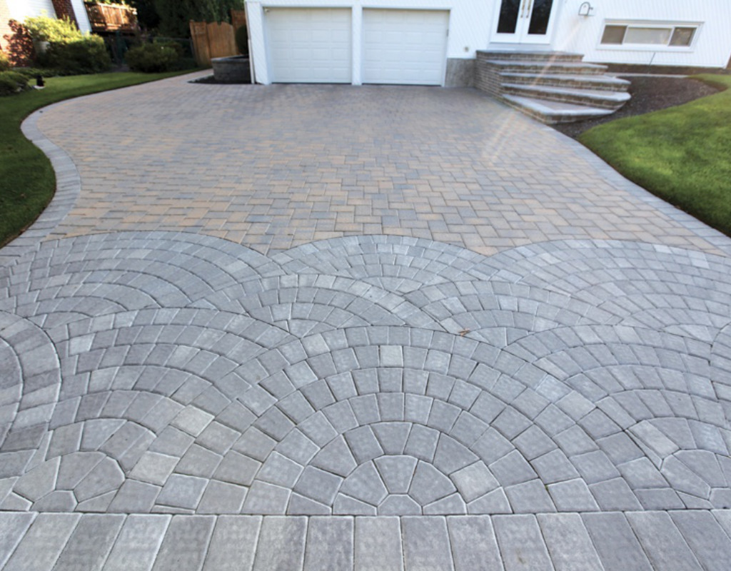 Multi colored stone driveway with walkway leading to the backyard
