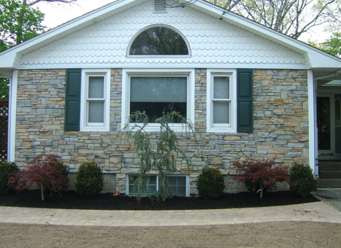 Natural looking stone veneers on the side of the house. Top part of the house has scalloped siding.