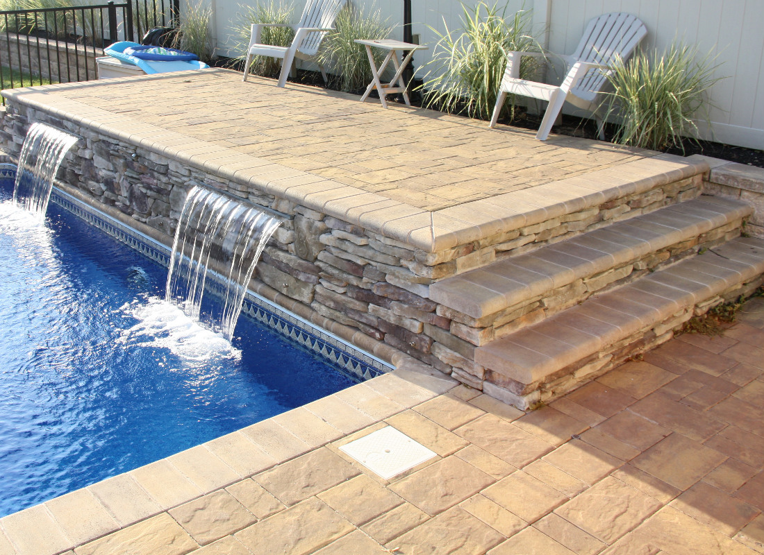 Waterfall from patio brickwork spilling into large in-ground pool