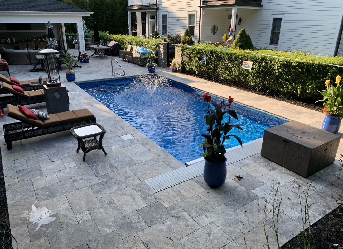 in ground pool with gray stone patio
