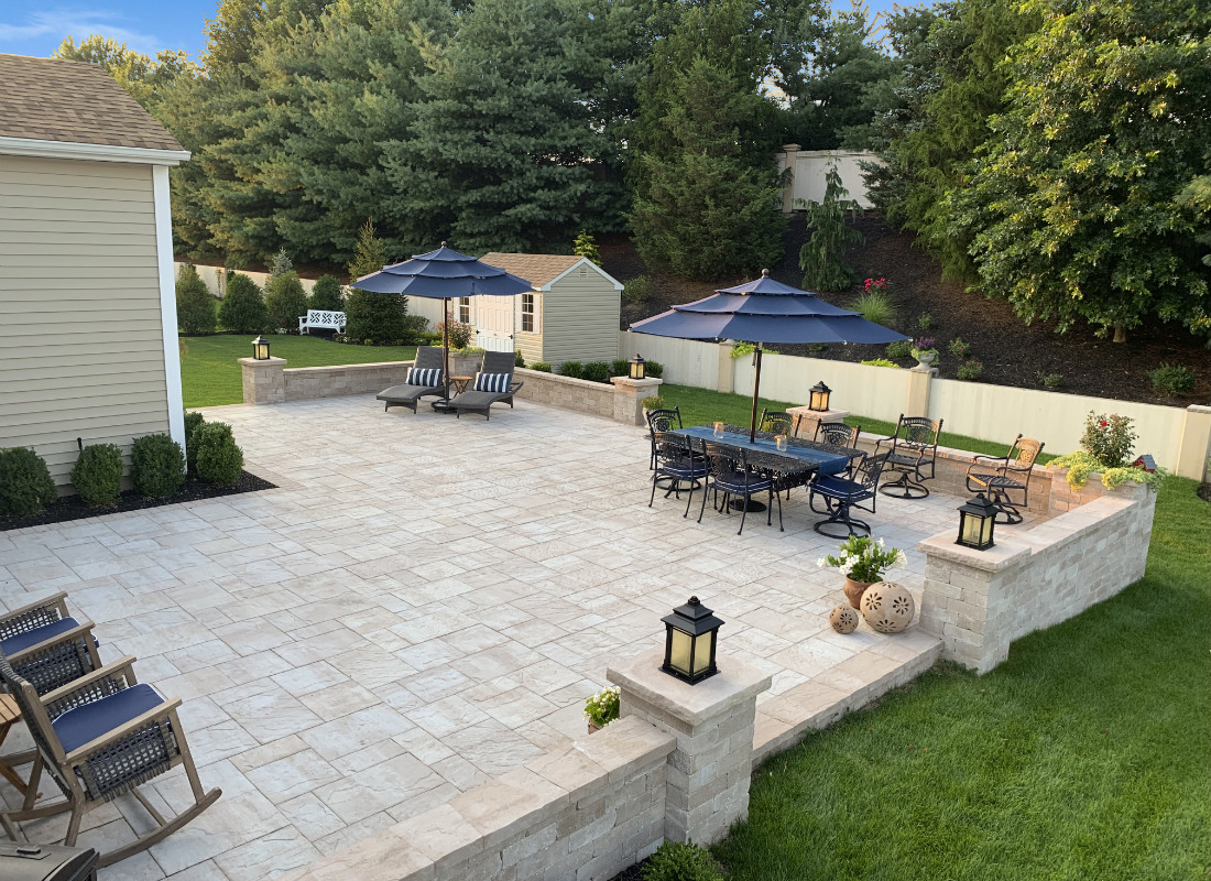 large patio with beige stones and barrier wall with lighting