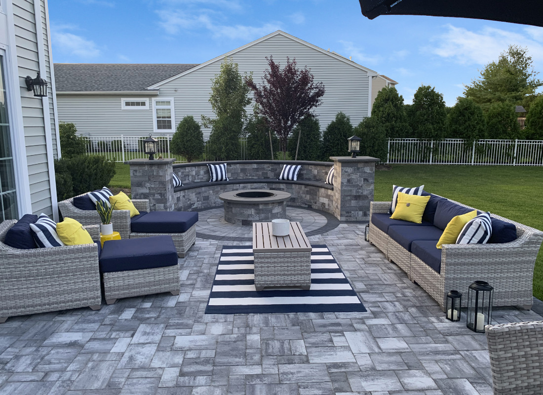 gray stone patio with fire pit and stone seating area