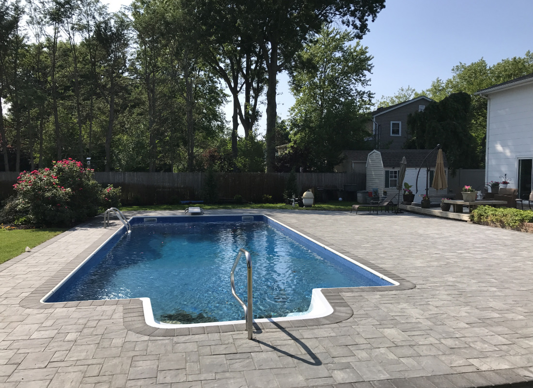 Traditional rectangular pool with gray brick work surrounding it