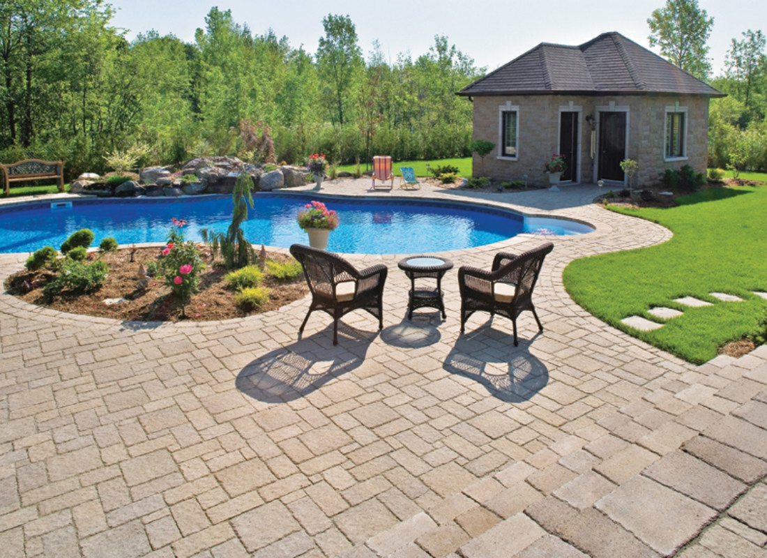 Kidney shaped pool with brick patio, seating area, flower bed, and pool house