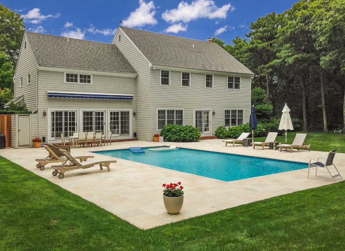 Large backyard in summertime with beige patio bricks