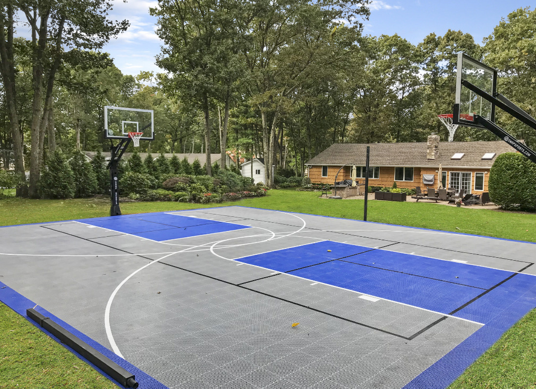 Full backyard basketball court with blue and gray floor