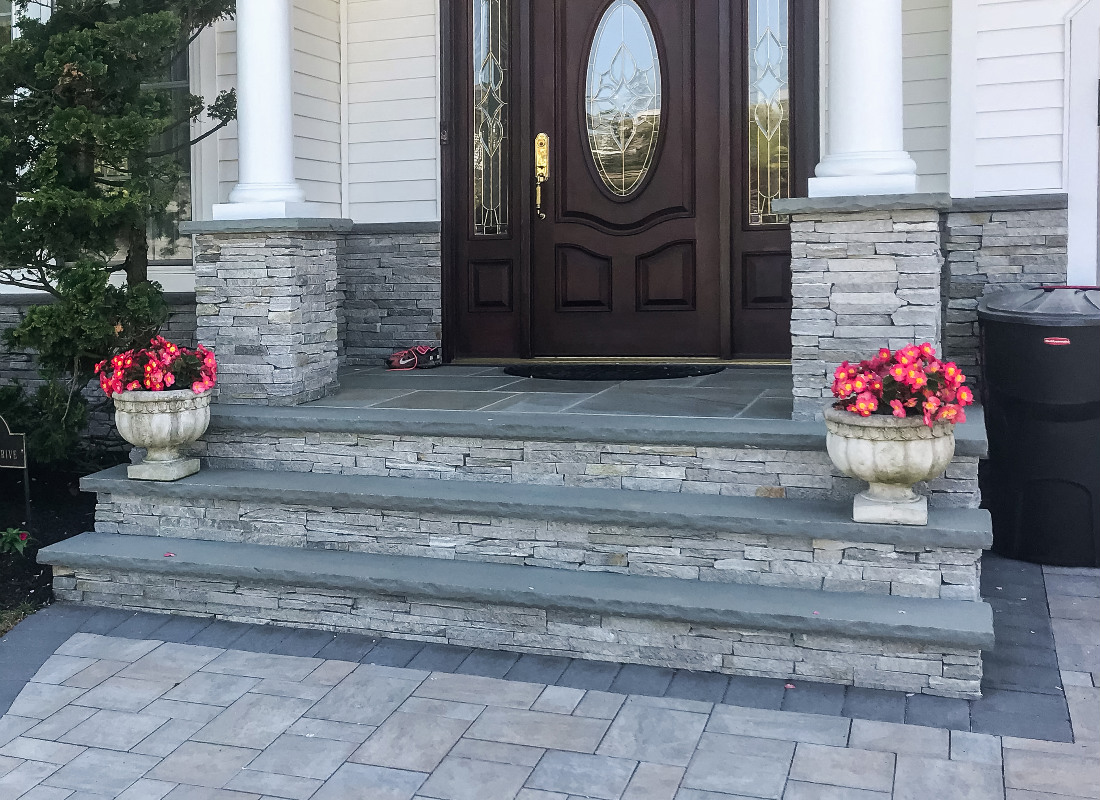 gray stone stoop with three steps with matching pillars and flower pots