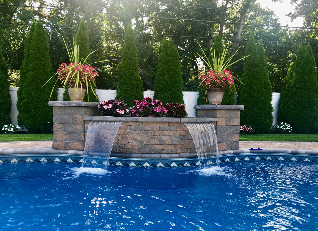 Double waterfall in brick stone wall complete with planters for flowers and greenery