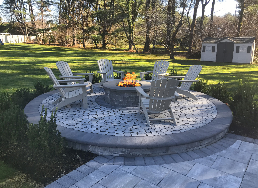 Elevated round patio made with stones with fire pit in the center