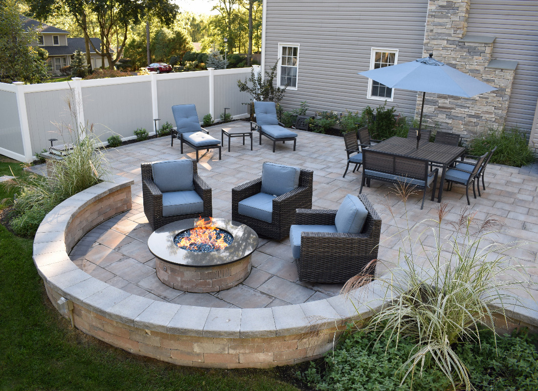 large square stone patio with half moon feature with seating and outdoor fireplace from side angle