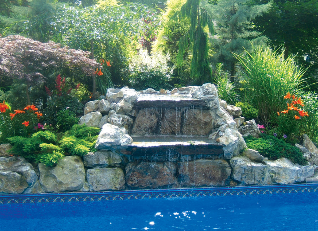 rock waterfall pouring into backyard pool