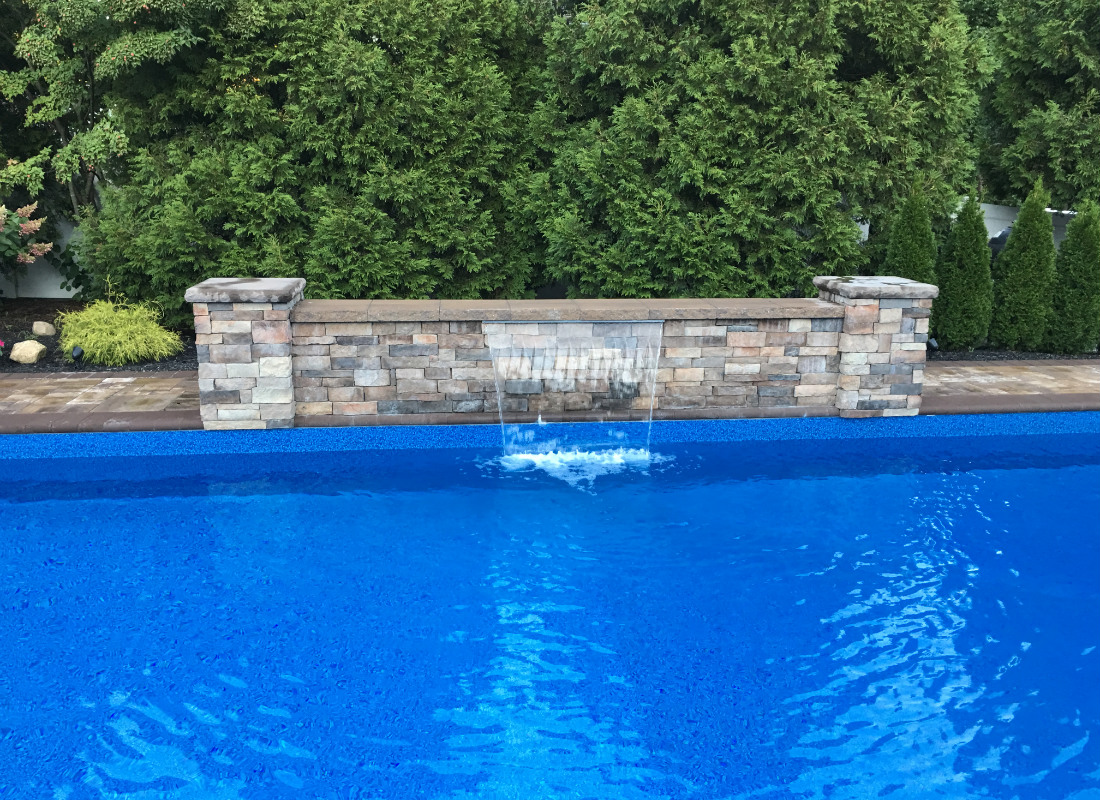 Single waterfall from a masonry design into a blue pool