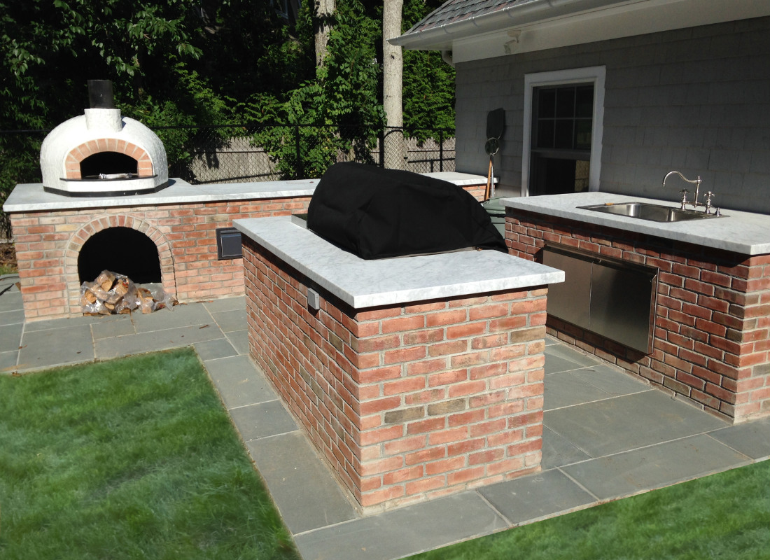 Outdoor kitchen with separate islands for BBQ grill, sink and stone oven