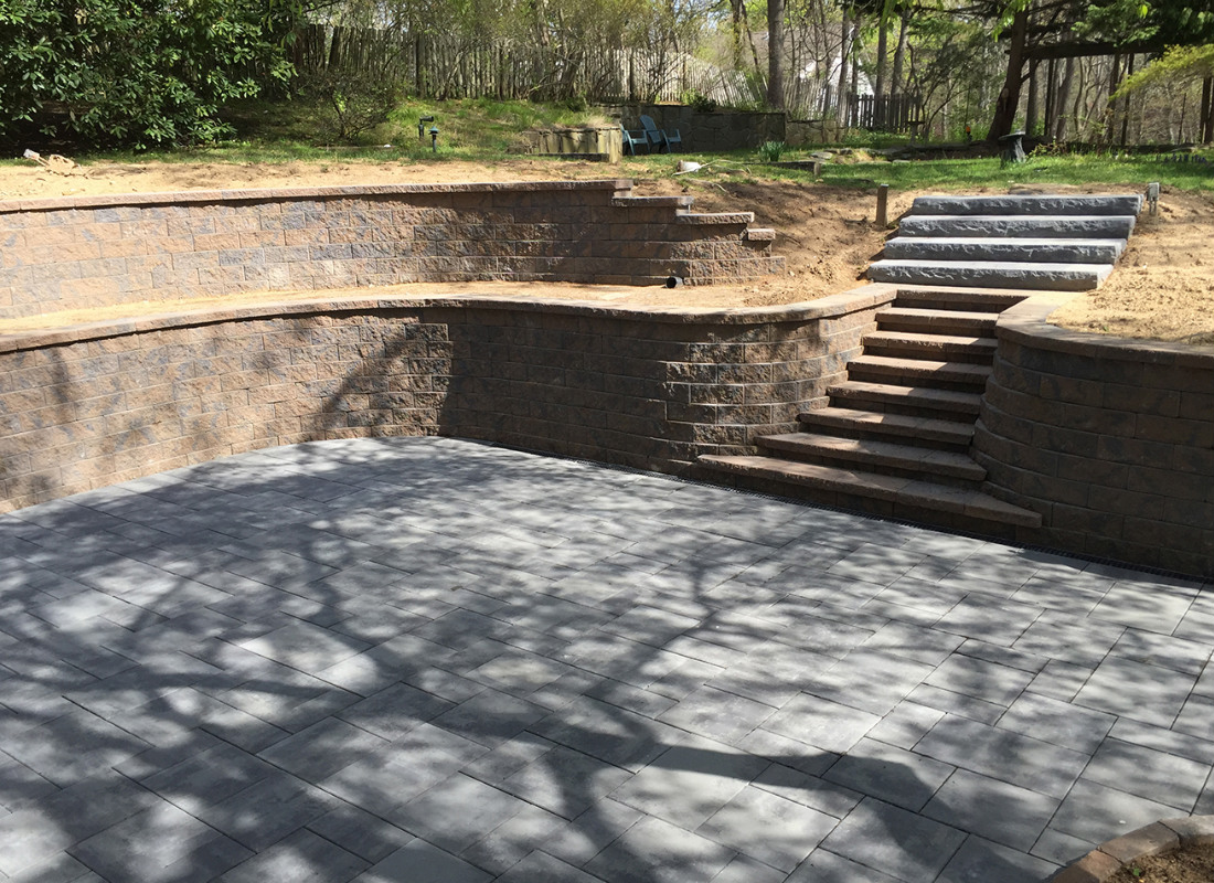 beige stone retaining wall with staircase in the center