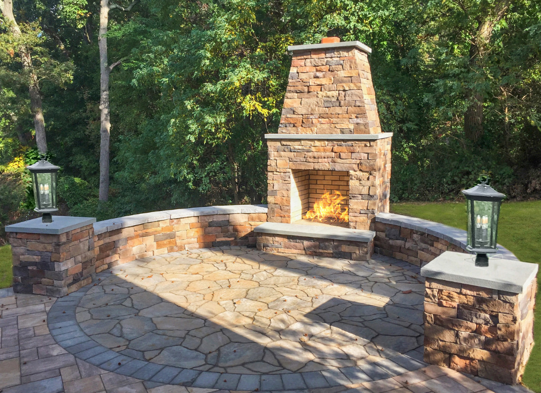 tall masonry fire place with chimney surrounded by stone veneer seating area