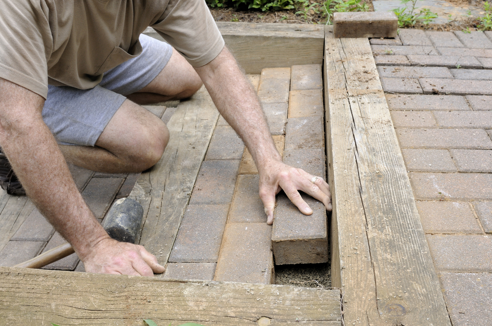 Worker Installing Brick Pavers