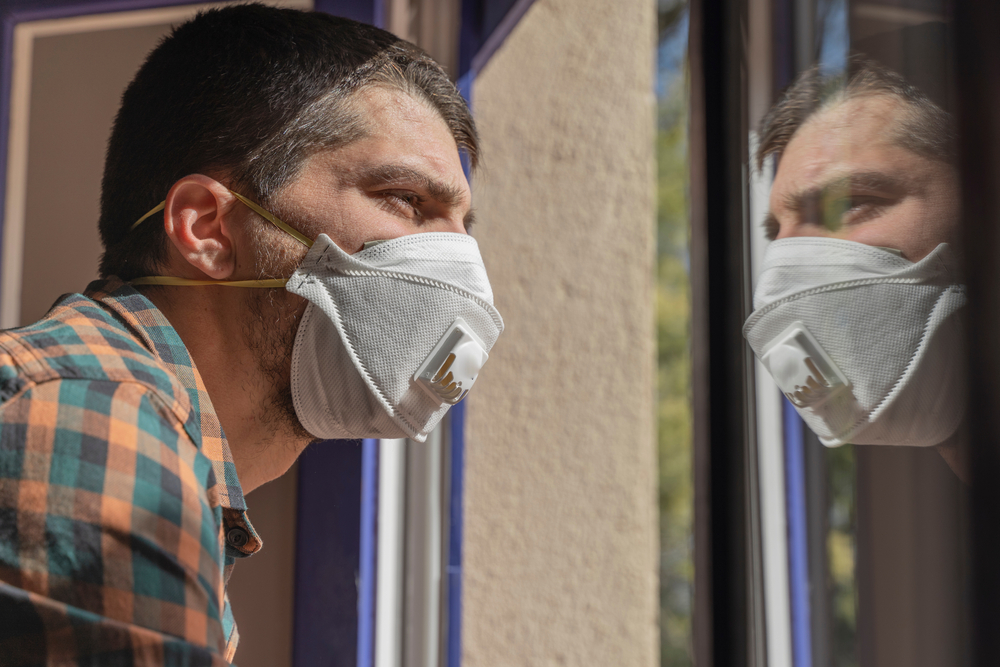 man quarantined at home looking at workers through the window