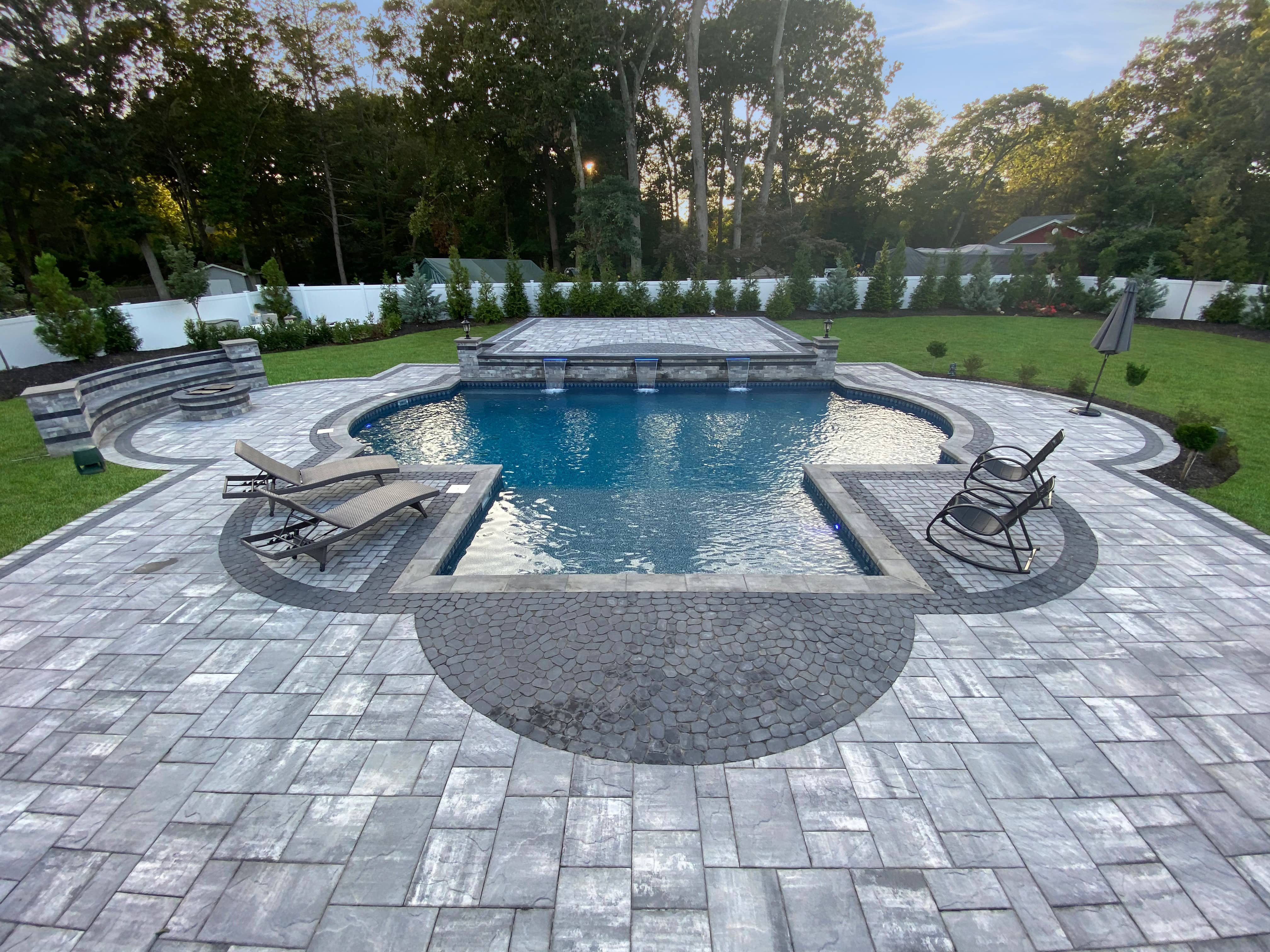 Custom Poolscape, brickwork pool surround, firepit, waterfall and lounge chairs, entertainment area