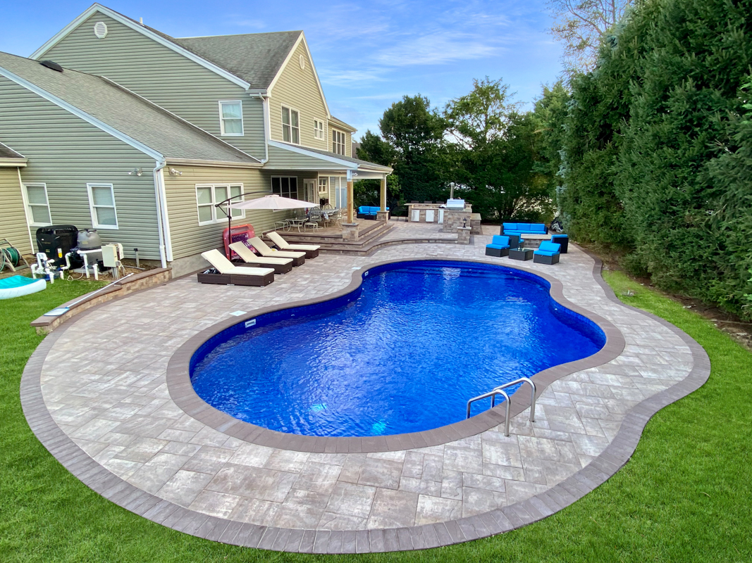 Pool on a property that sits on the shoreline with retaining wall and masonry patio
