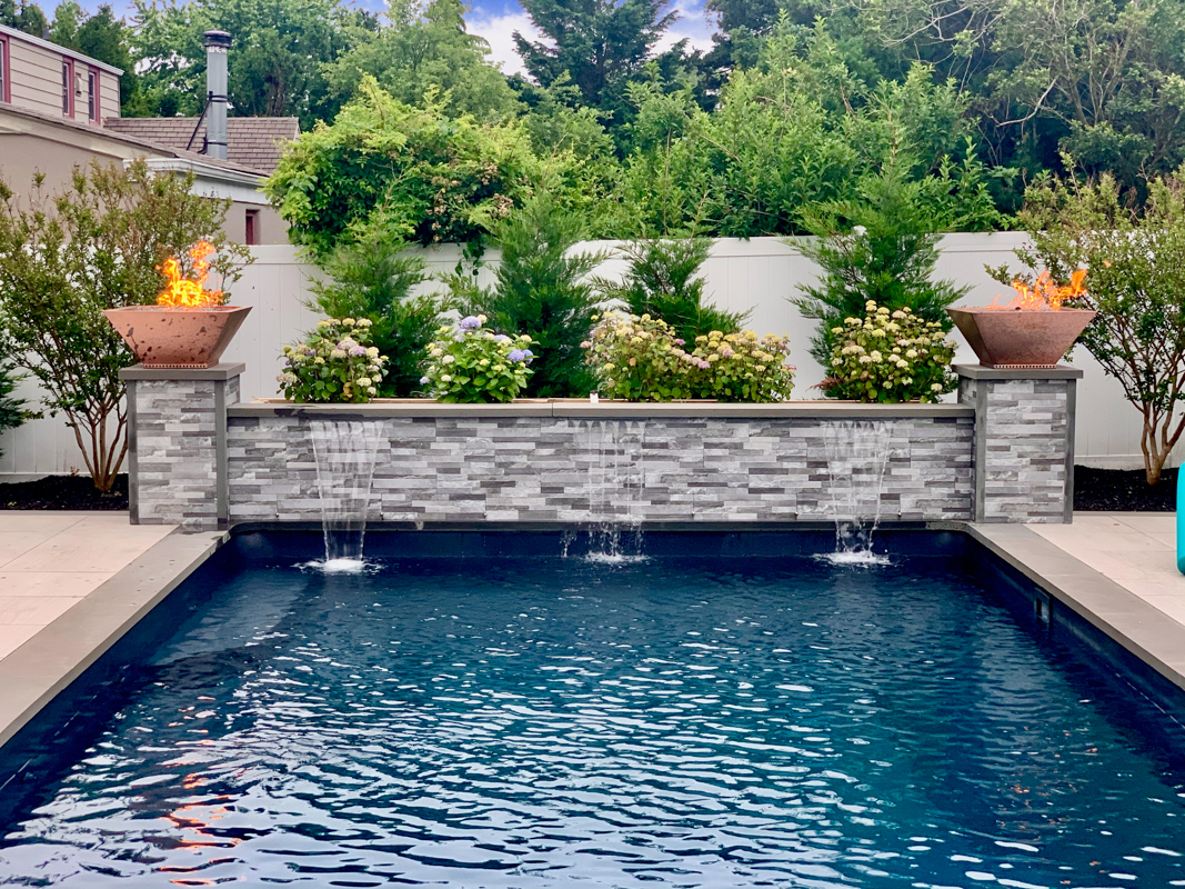 Two water falls descending from masonry patio into pool